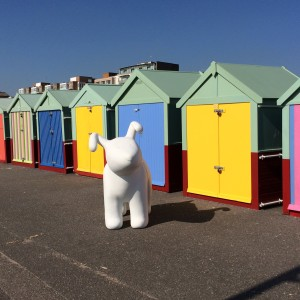 A model of Snowdog in front of beach huts.